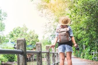 カメラの呼吸と熱帯の歩道と運河、アジアの観光旅行者を見てヒップスターのアジアの女の子