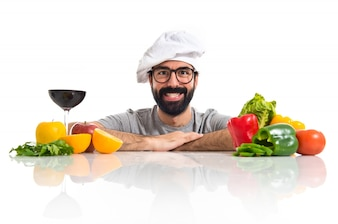 Hipster chef with several vegetables and fruits on table