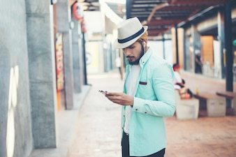 Hipster man listening music with his smartphone on the street in urban.