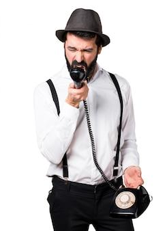 ビンテージの電話に話すひげの男