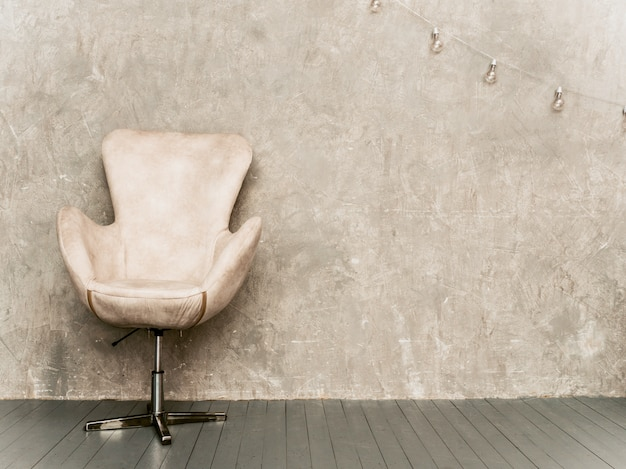 Home interior gray wall background with beige velvet armchair, and wooden floor