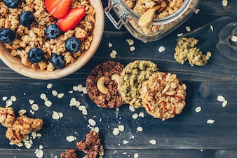 Homemade granola and fresh berries on wood table with space.