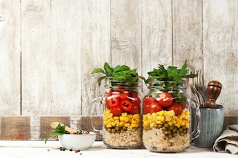 Homemade healthy layer salad in mason jars on a wooden backgroun