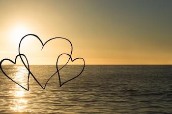 Horizon at sunset with three hearts drawn