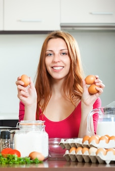 Housewife in red with eggs in home kitchen