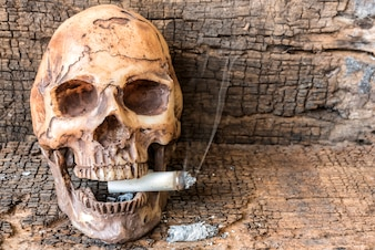 Human skull smoking cigarette with smoke