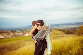 Husband carrying his wife on his shoulders