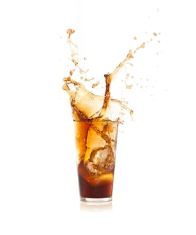 Ice falling into a glass with brown drink