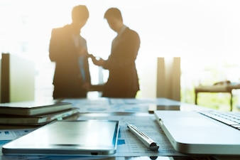 Image of business  workplace with team partners interacting on background.