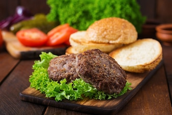 木製の背景に牛肉、ピクルス、トマト、赤い玉ねぎとサンドイッチ - ハンバーガーハンバーガーのための材料。