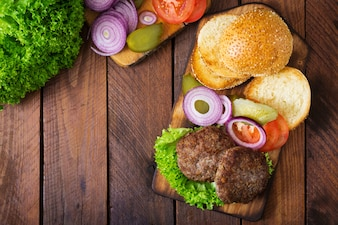 Ingredients for a sandwich - hamburger burger with beef, pickles, tomato and red onion on wooden background.