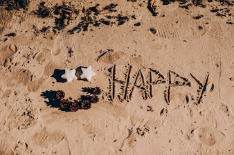 Inscription 'HAPPY NEW YEAR' and human footprint in the sand on the beach