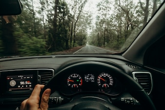 Inside view of car steering wheel while driving across Australian road.