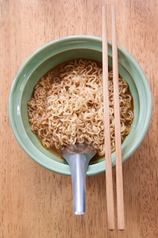 Instant noodle with spoon and chopsticks in a ceramic bowl on wood background