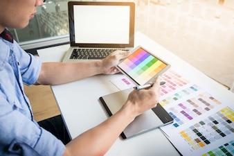 インテリアデザインまたはグラフィックデザイナーの改装と技術コンセプト - 選択のためのカラーサンプルを使用している女性。