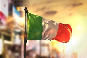 Italy Flag Against City Blurred Background At Sunrise Backlight