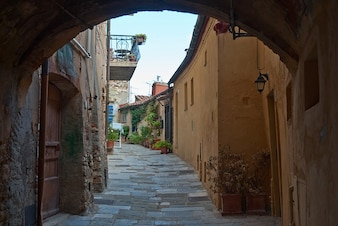 italy sidewalk stone arch buildings town alley