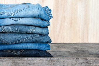 Jeans stacked on a wooden table