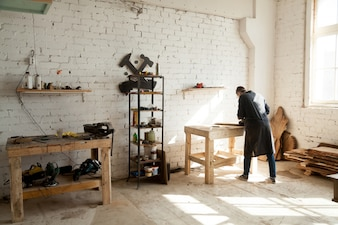 Joiner working at workbench in small carpentry
