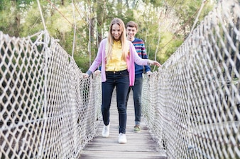 Joyful couple crossing a wooden bridge