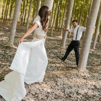 Joyful couple playing among the trees