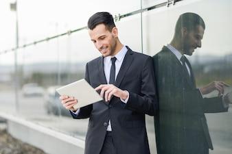 Joyful employee using his tablet