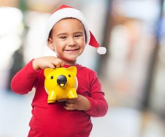 Joyful little boy with piggybank and santa claus hat