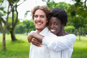 Joyful mix-raced couple cuddling in summer park