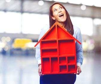 Joyful woman holding a wooden house