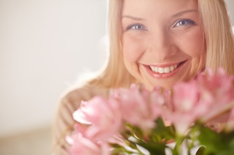 Joyful woman with pink flowers