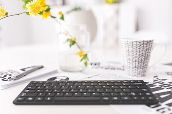 Keyboard with yellow flowers and a cup