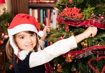 Kid decorating a tree on christmas