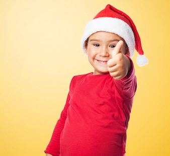 Kid smiling with thumb up and santa's hat