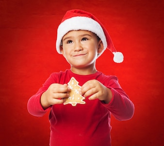 Kid with a cookie tree in a red background