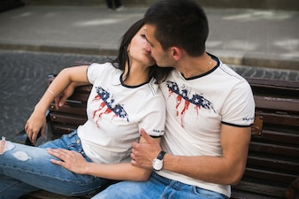 Kissing couple in similar t-shirts on bench