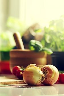 料理のコンセプトを調理するキッチンの背景。テーブル上のタマネギ。テーブルの野菜。クッキングプロセス。トーニング