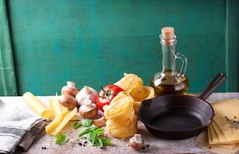 フライパンや生パスタを備えたキッチンテーブル