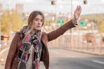 彼女の腕を上げるタクシーを求める若いハンサムな白人の茶色のストレートヘアーの女性の膝の図 - 技術、コミュニケーション、輸送のコンセプト