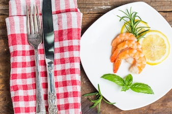 Knife and fork next to a dish with cooked shrimps