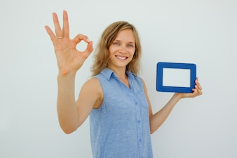 Lady Holding Picture Frame and Showing OK Sign