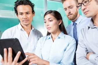Леди, показывающая информацию о планшете для коллег