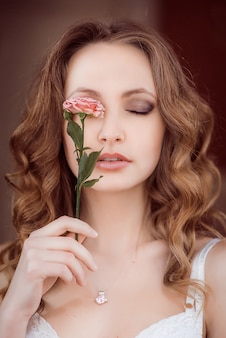 Lady with curly hair holds pink rose before her eyes