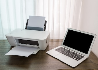 Laptop on a wooden table with a printer