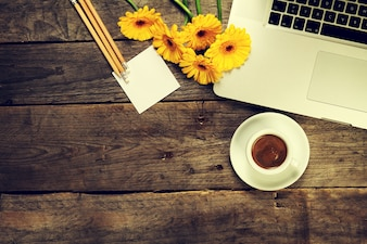 Laptop with a cup of coffee and flowers