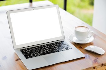 Laptop with blank screen next to a cup of coffee