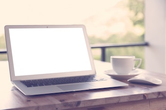 木製のテーブルやコーヒーカップに空白の画面を持つラップトップ