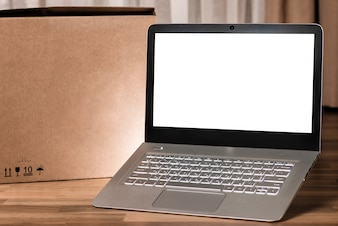 Laptop with blank screen on wooden table and blurred background