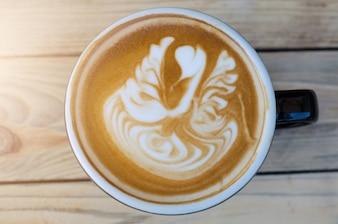 木製の背景にラテアートコーヒー