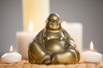 Laughing buddha figurine and lit candles on mat