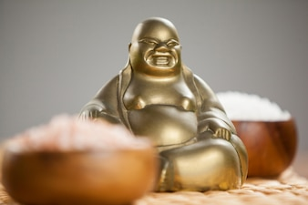 Laughing buddha figurine and sea salt in wooden bowl